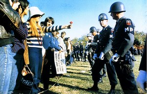 "one of those historic ""flower power"" moments in California protesting the Vietnam war. The girl offers the soldier a flower."