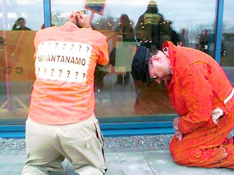 orange jumpsuits kneel outside Galway restaurant window to protest US ambassador