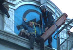 riot cops in cherry picker pluck defender of space from Miles roof