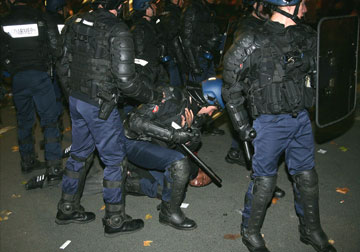 French police arrest a protester who was taking part in National Union demonstration against retirement reform in Paris last night. (Is France racist?)
