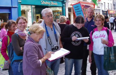 Italians from Umbria signing the petition with Andy holding placard.