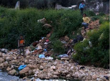 Palestinian children play in a polluted stream contaminated by wastewater from Ariel settlement, Bruqin, West Bank. (Photo: EWASH-OPT)