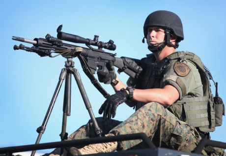 One of the heavily militarised police in Ferguson points his military sniper rifle at peaceful protesters