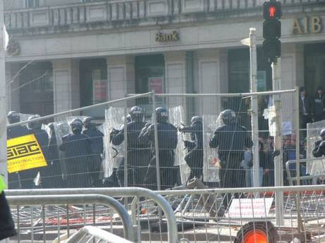 Riot Police Advance Through the Building Site