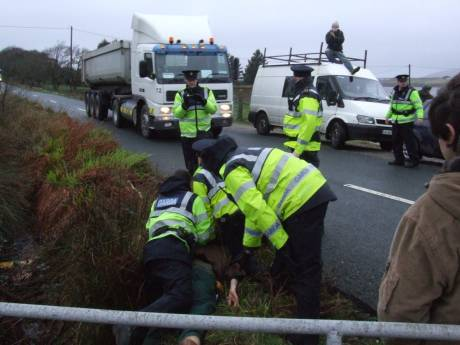 Person being held down in the brambles while Shell's convoy passes