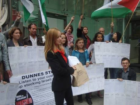 Freda Hughes IPSC Chairperson holding 6,000 signatures calling on Dunnes to stop stocking Israeli produce