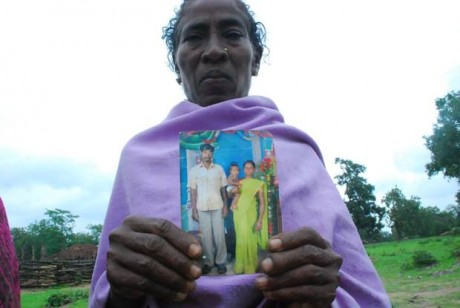 Villager shows photo of murdered loved one.