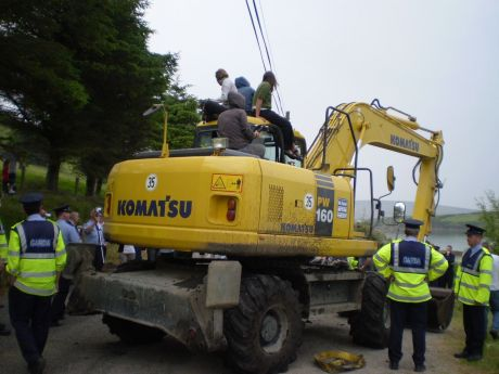 Protesters climb on the digger.