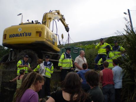 The digger hoists the illegal portacabin into place.