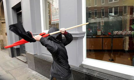 protester tries to break a window in Oxford Street during the anti-cuts march