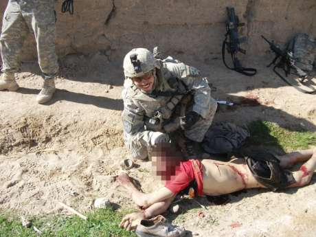 In this image, a different soldier poses with the same corpse.