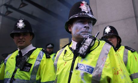 Paint-splattered police officers look on as protesters attack Topshop on Oxford Street during the anti-cuts march in London