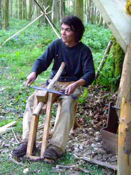Shaping a leg on the shave-horse with a drawknife.
