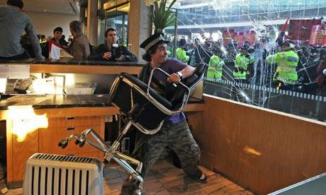 Student protesters smash windows as they clash with police after entering Tory HQ at Millbank Tower, London.