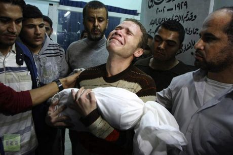 BBC correspondent Jihad Masharawi weeps as he cradles his 11-month-old son in his arms after he was burned alive during an Israeli rocket attack.