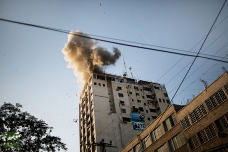 Smoke billows as debris flies from the explosion at the local Al-Aqsa TV station in Gaza City on November 18, 2012 after it was attacked during an Israeli airstrike. An Israeli air strike hit a Gaza City media building.(AFP Photo / Marco Longari)