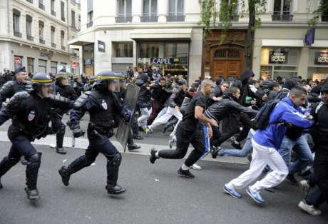 Protesters run during clashes in Lyon