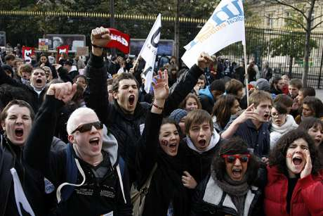 Students shout slogans as they demonstrate with union workers in Paris against raising the retirement age to 62
