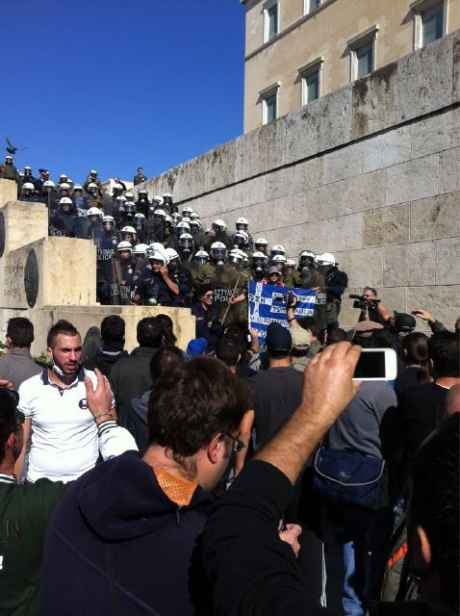 Angry greeks at steps of parliament, which is filled with riot squad