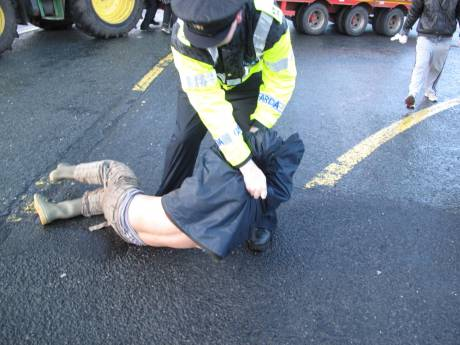Protester being dragged away from the tractor