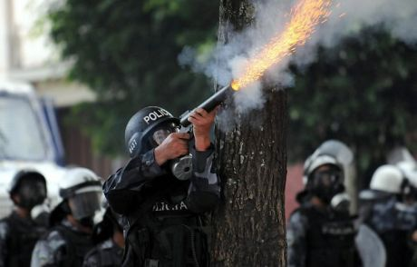 third world cop wearing Kevlar body armour firing tear gas canister at civilians outside the Brazilian embassy to Honduras